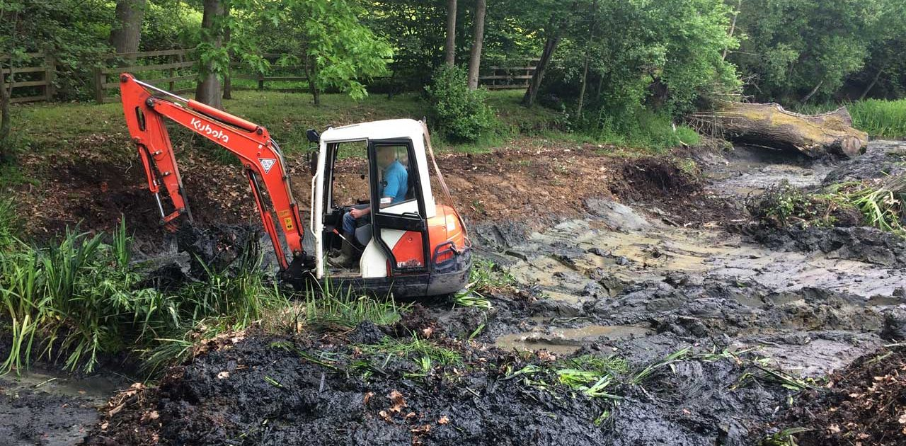 Image of a Kubota excavator clearing the side of a lake and preparing the ground works ready for traditional clay lake relining at Barkham in Berkshire - Let the digger do it!