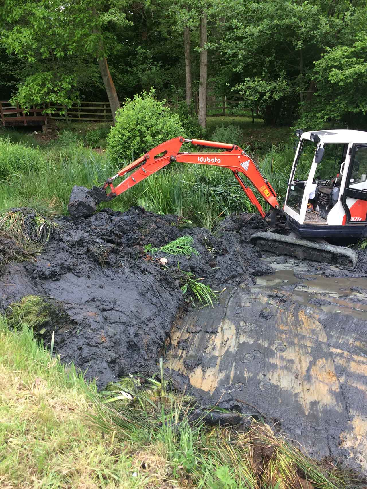 Image of a Kubota excavator clearing a lake ready for traditional clay lake relining at Barkham in Berkshire - Let the digger do it!